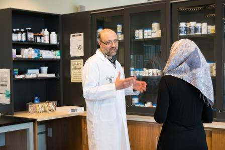 Pharmacist helping a patient wearing a headscarf.