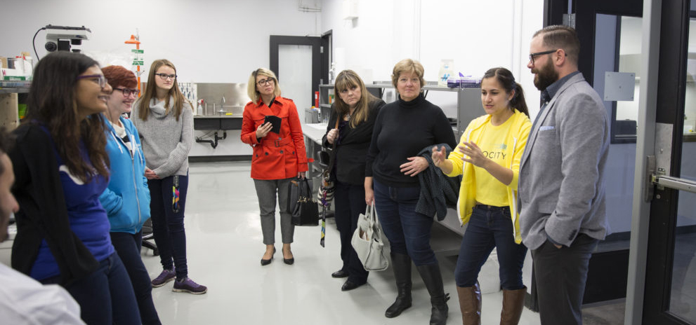 Velocity Science co-op Sabrina talks to a group in a lab