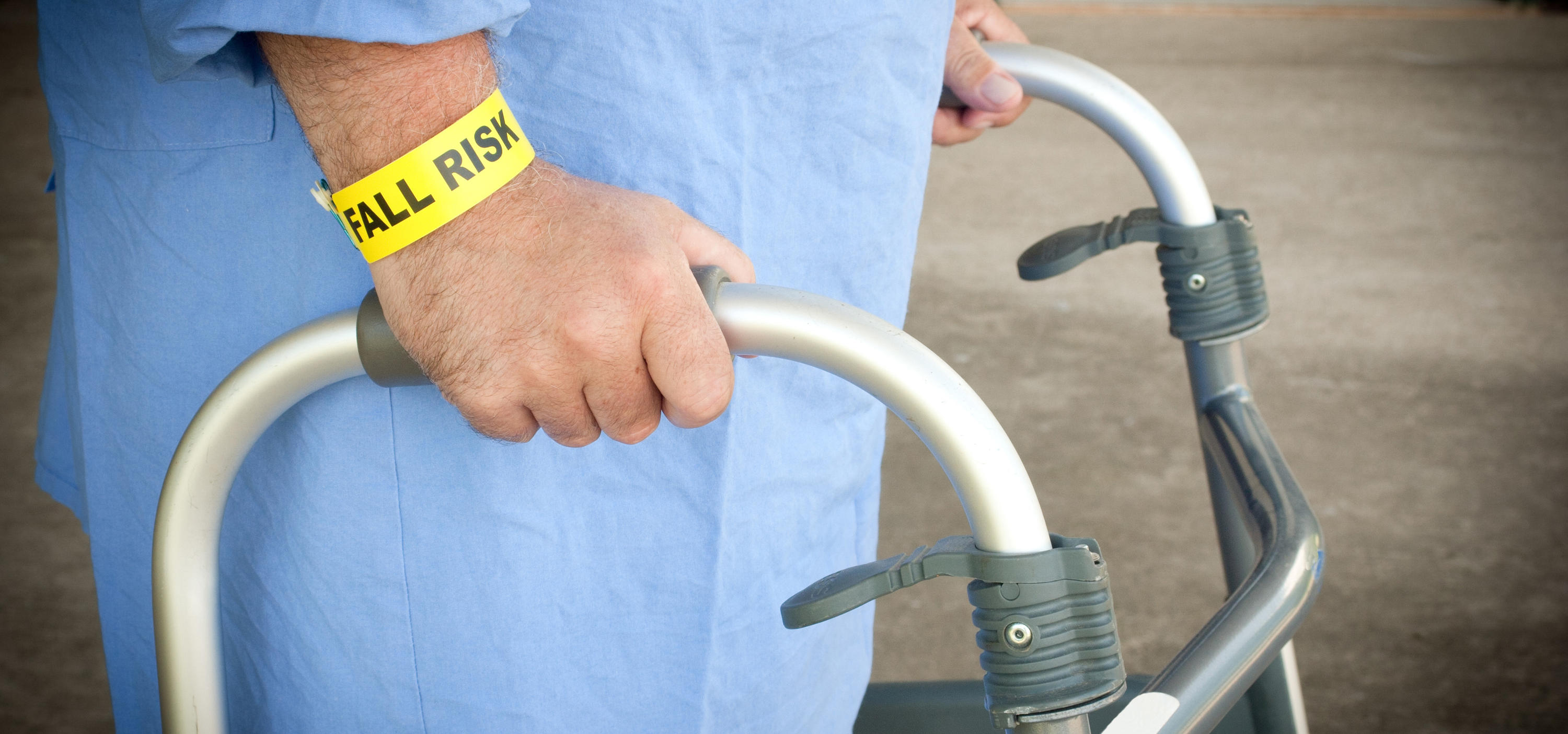 A hospital patient wearing a fall risk bracelet and using a walker.
