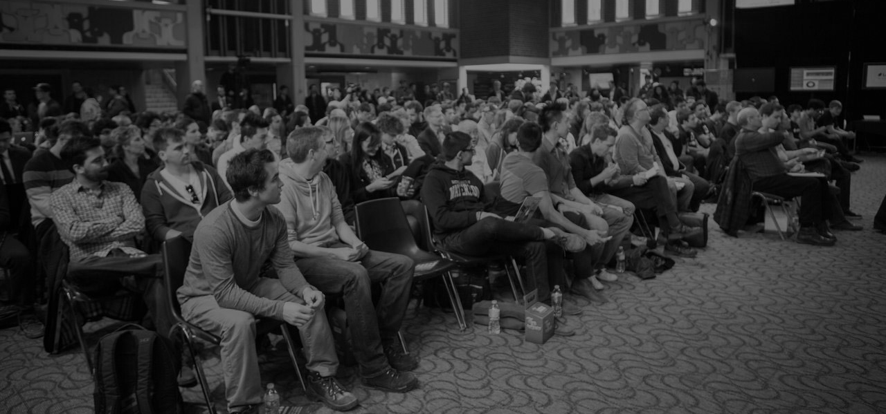 Black and white photo of audience watching a pitch.
