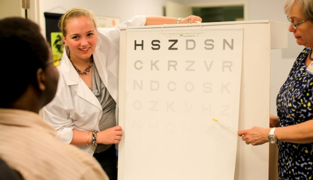 Client viewing Pelli-Robson contrast sensitivity chart while optometrist points to a letter and an intern observes.