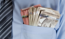 Money in a man's shirt pocket.
