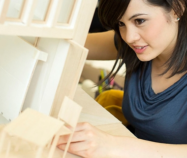 A female student arranges a 3D architectural model