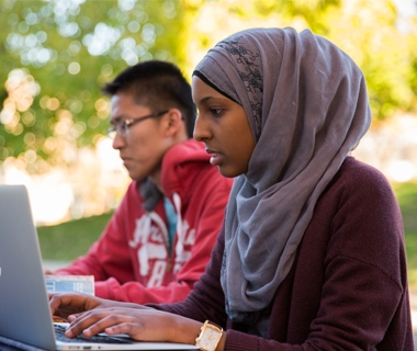 Two students on a laptop