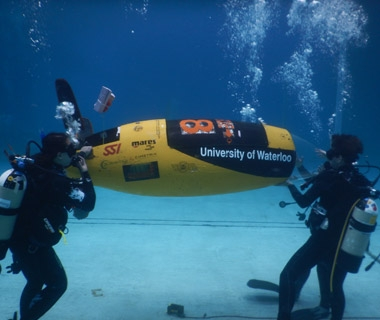 Members of the WatSub team race their submarine, AMY