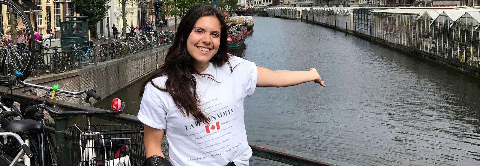 Student gesturing to the canal she is standing in front of.