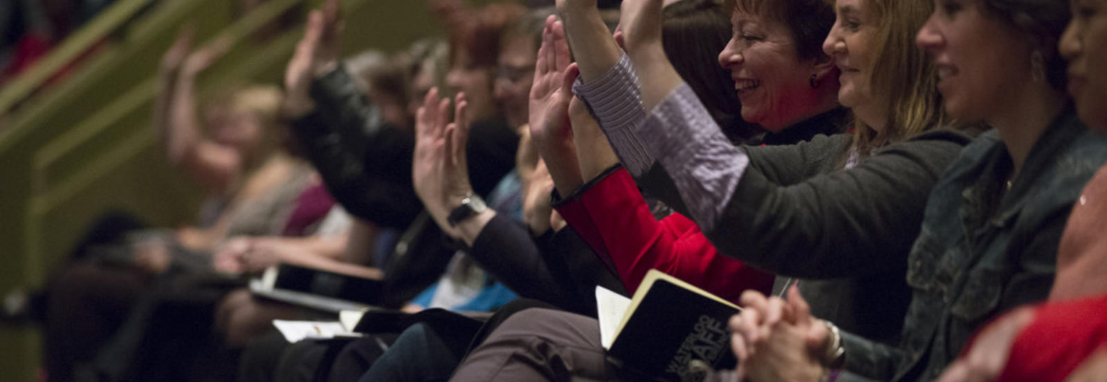 Staff members raise their hands at a conference