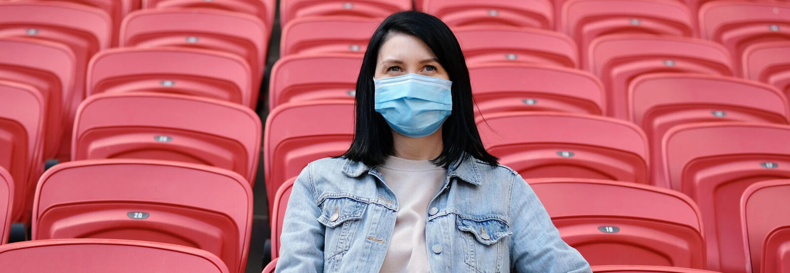 Woman with mask sitting in stadium bleachers