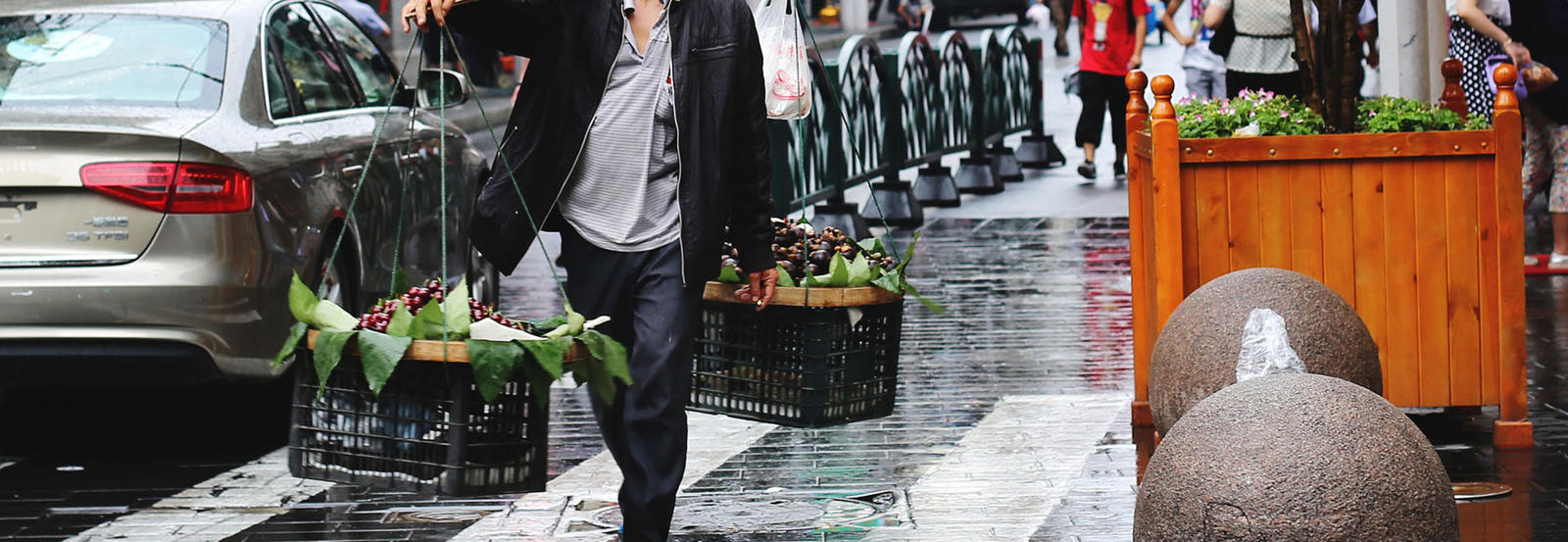 an elderly man walking down the street holding baskets of food