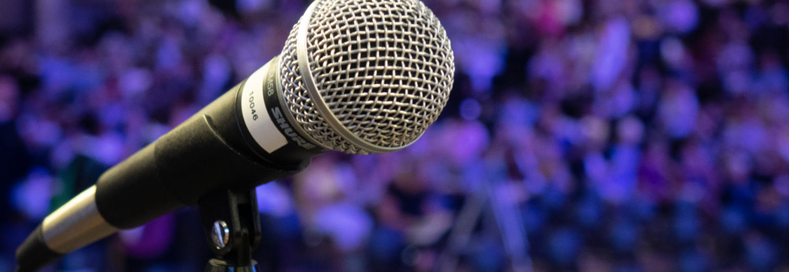 A close up of a microphone in front of a crowd