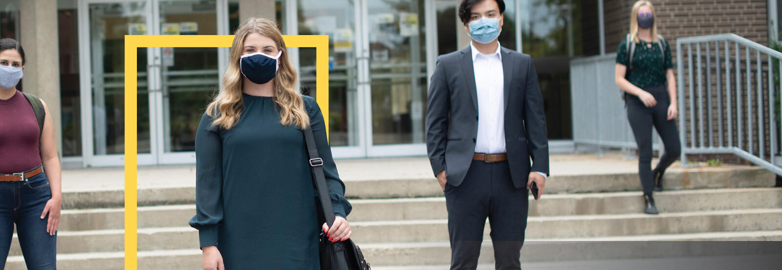 students wearing masks outside of a campus building