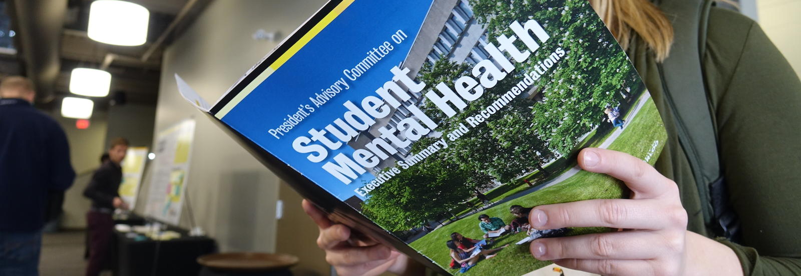 Girl reads the student mental health executive summary.