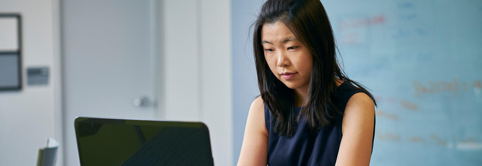 Close up of female student in business casual working on a laptop