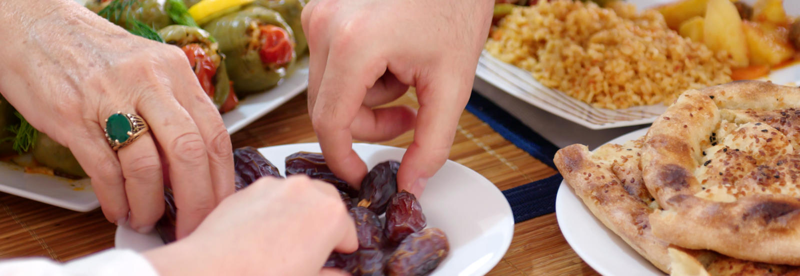 Three hands reach for a plate of dates.