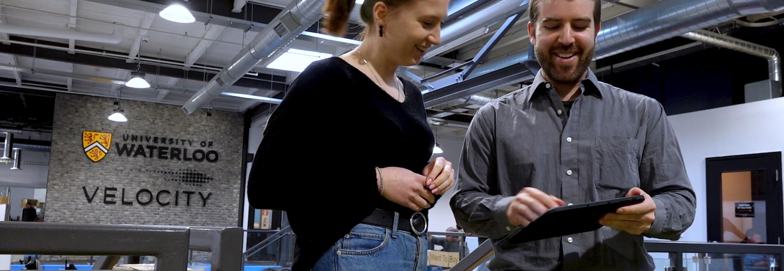 Mr Harris showing a woman an ipad