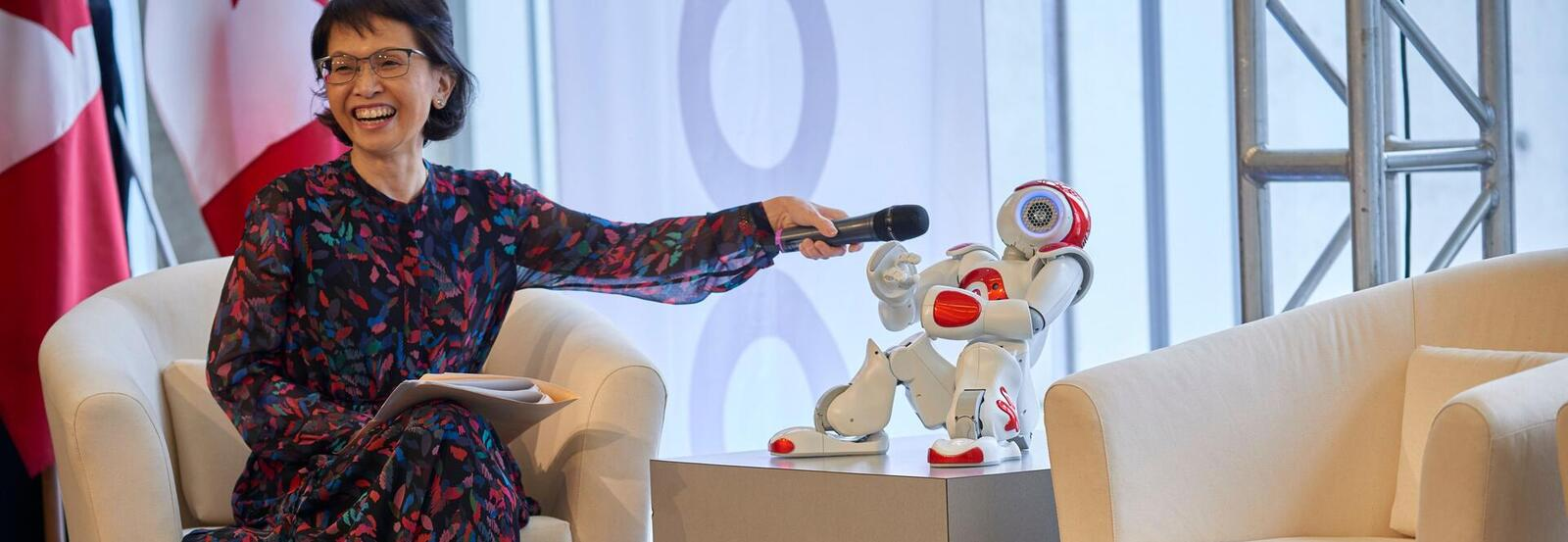 Pearl Sullivan holding a microphone to a robot