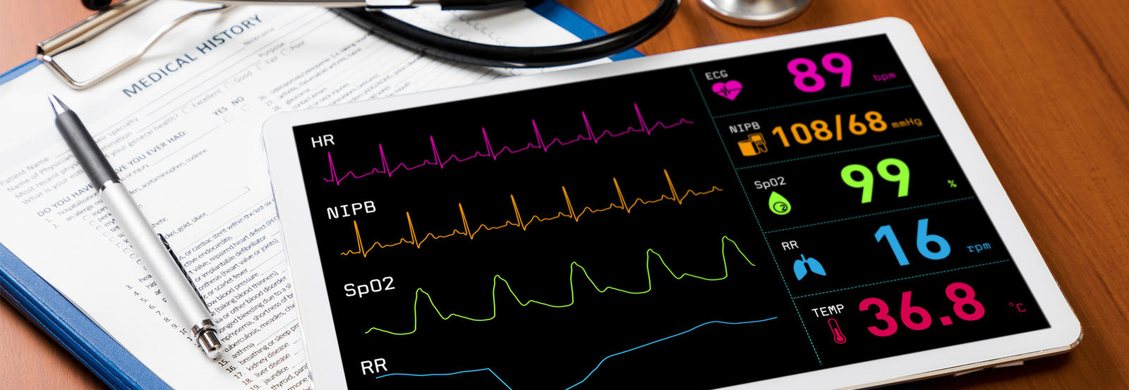 Image of an ipad with heart monitor information on it beside medical tools and clipboard.