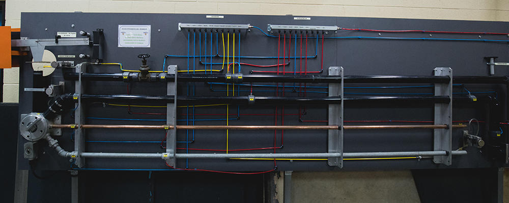A wall with tubing of different colours and materials