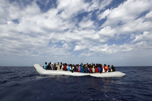 Raft full of people in the middle of the ocean.