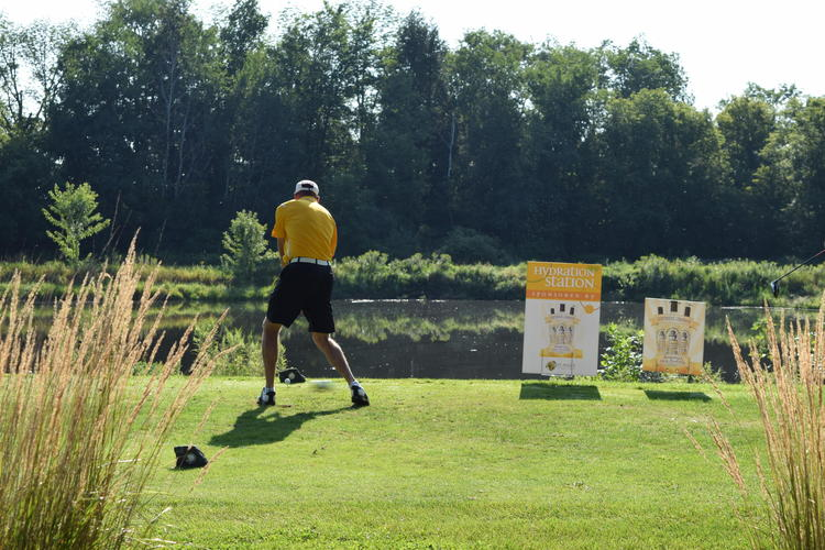 Golfer wearing yellow shirt tees off with grass in foreground and sponsor signs in background