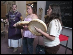 Two students being taught how to drum by a community member.