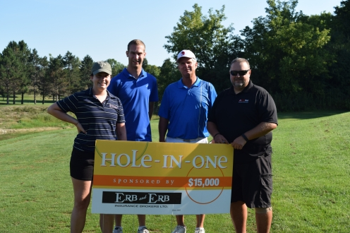 four golfers pose with sponsor sign