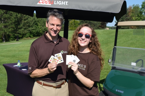 two volunteers pose with playing cards