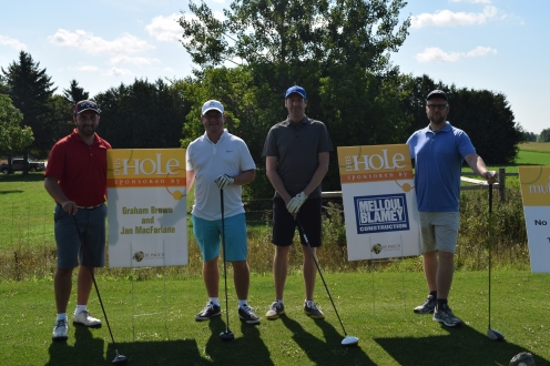 four golfers pose with sponsor signs