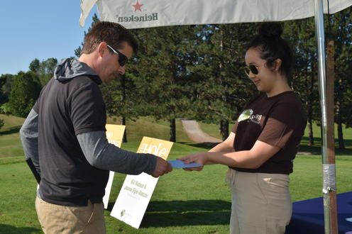 golfer chooses a playing card from a student volunteer