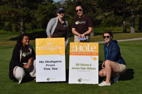 volunteers pose with a hole sponsor sign