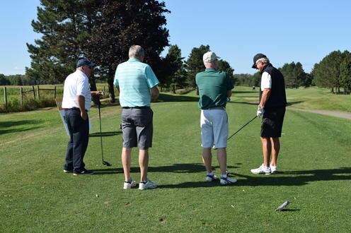 four golfers huddled on the tee box preparing for their next shots