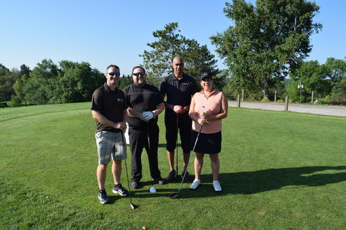 foursome posing on tee box