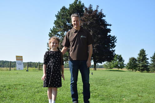 Principal Myers and his daughter pose together with trees in background