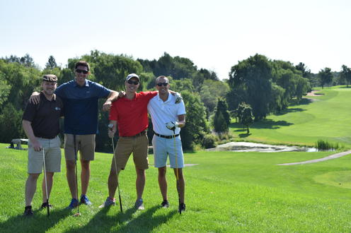 foursome poses with trees and fairway in background