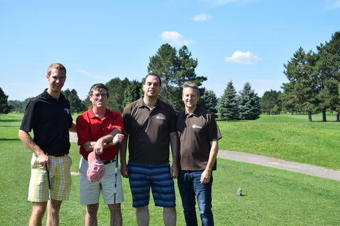 three golfers pose with Principal Myers