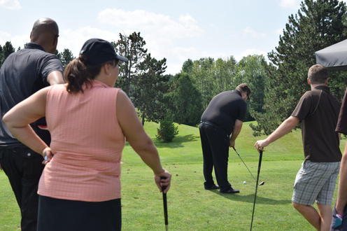 three golfers look on as their teammate prepares to hit an iron shot