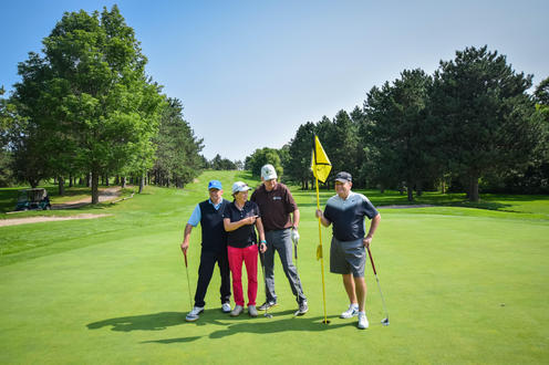 a group of four golfers posing