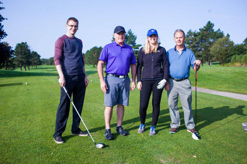 group of four golfers poses together