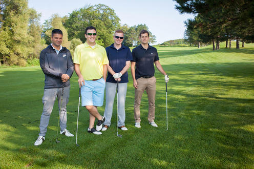 group of four golfers pose together