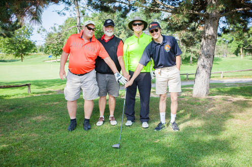 group of four golfers posing together