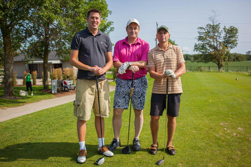 group of three golfers posing together