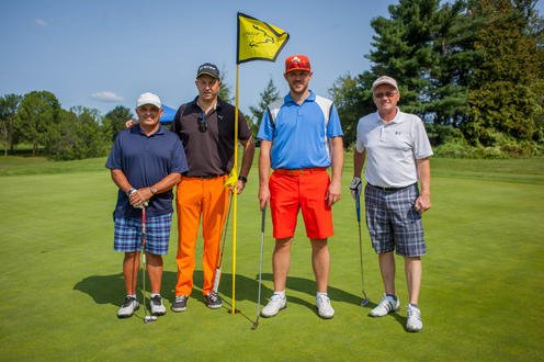 group of four golfers posing with flag stick in background