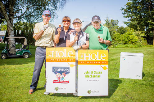 group of four golfers pose with ice cream and sponsor signs
