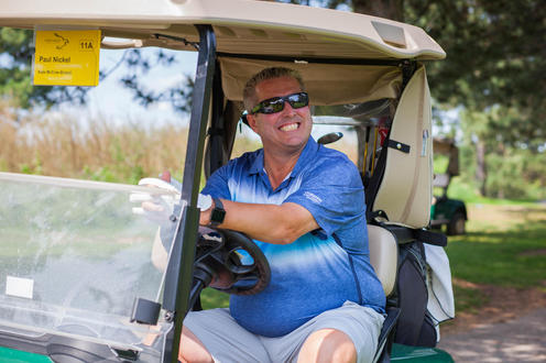 golfer on a cart smiling at the camera
