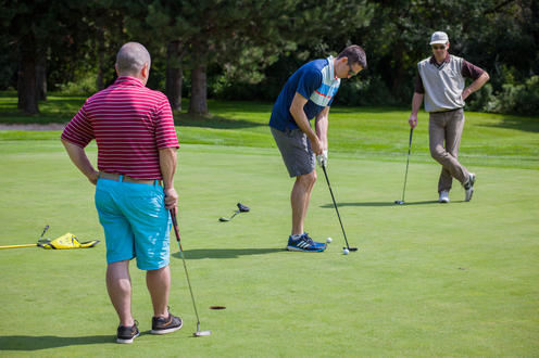 two golfers looking on as member of group attempts a putt