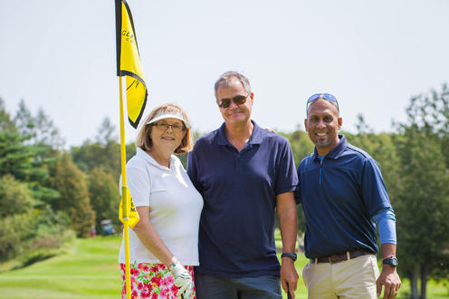 group of three golfers poses together