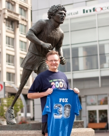 Bill Pristanski poses beside the Terry Fox monument with 30th Terry Fox Run t-shirt