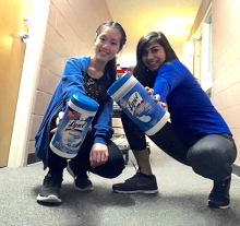 Students holding cleaning supplies.