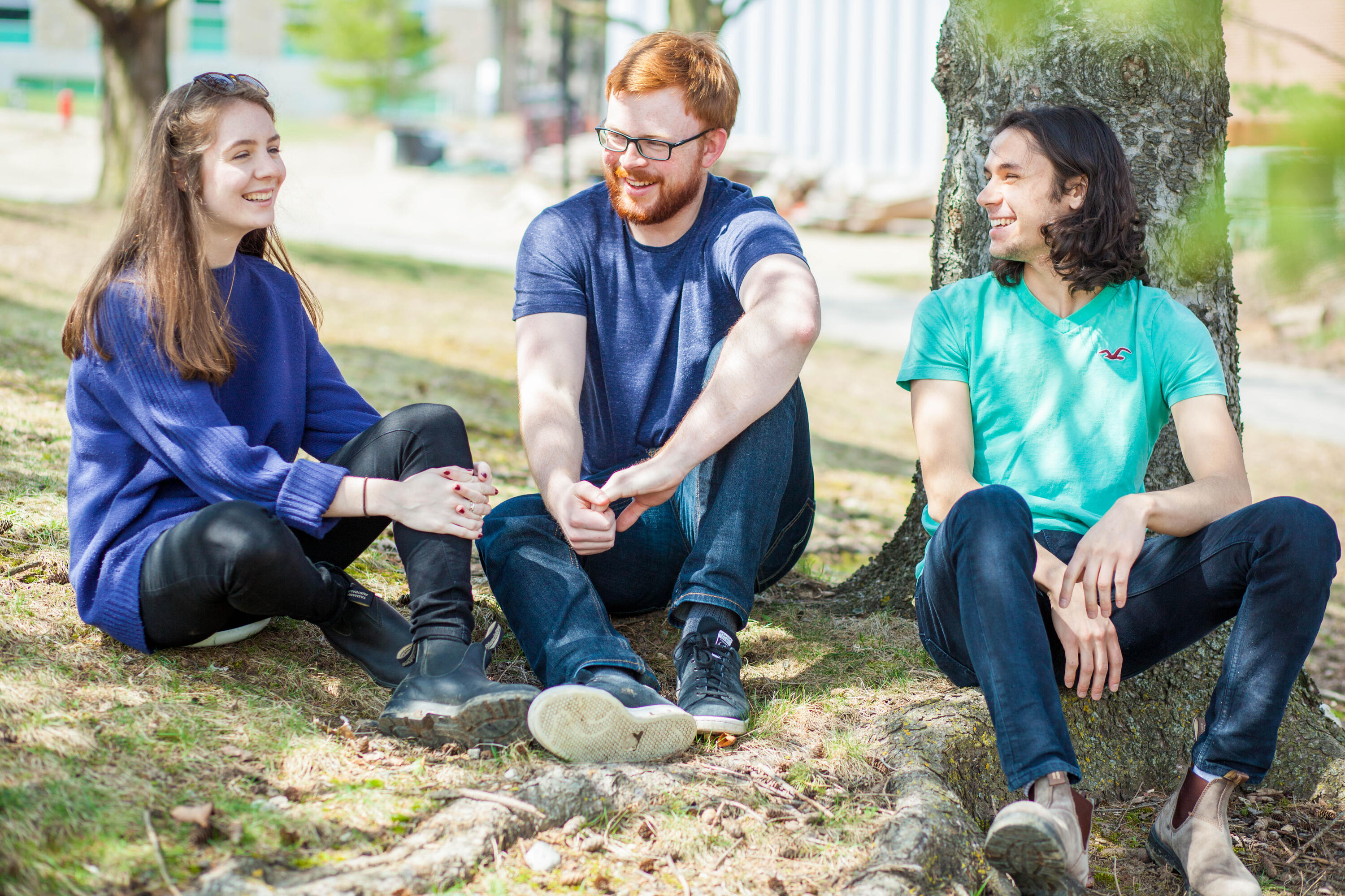 Three students sitting outside beside a tree
