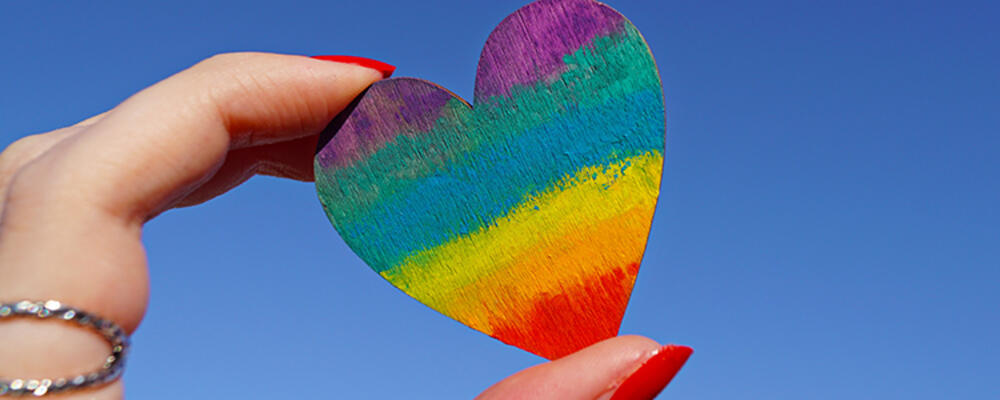 Hand holding a rainbow painted heart